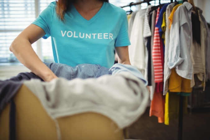 Female volunteer holding clothes in donation box